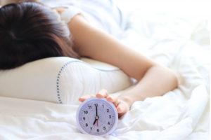 目覚まし時計を押さえている女性の写真です。